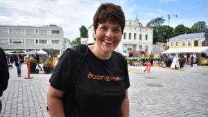 Kvinna med svart skjorta och mörkt hår ser mot kameran och ler. Torg i bakgrunden.