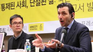 Bequelin framför en banner med Amnestys logo och text på koreanska.