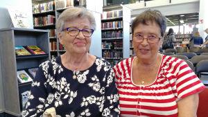 Två kvinnor sitter på stolar i ett bibliotek.