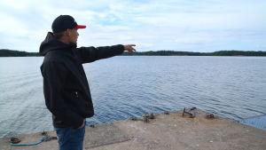 En man iklädd svart jacka och keps står och pekar ut på havet