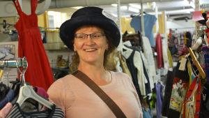 Kvinna på en loppmarknad iklädd en rolig hatt.