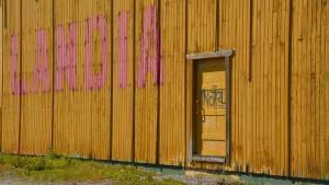 Staketet till Wasalandia med graffiti på dörren.