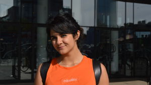 En tjej med svart hår och orange t skjorta ler mot kameran.