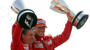 Jean Todt och Michael Schumacher håller om varandra och lyfter varsin pokal.