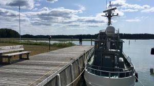 ett fartyg ligger förtöjt vid en brygga.