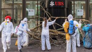 Ungdomarna lyfter upp trädgränar framför bankens ingång.