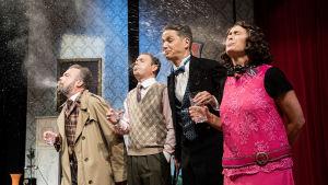 Fyra skådespelare med whiskyglas i handen spottar ut vätskan de nyss har druckit.
