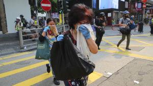Förbipasserande försöker skydda sig mot tårgasen under söndagens demonstration i centrum av Hongkong.