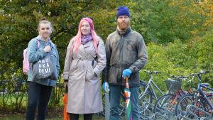 Tre unga personer står på rad framför några cyklar och ser allvarsamt in i kameran.