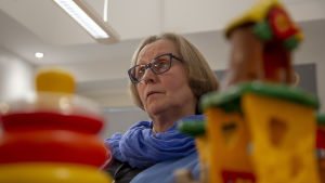 Rauman kaupungin sosiaalityöntekijä Päivi Toivonen istuu tuolilla neuvotteluhuoneessa lastenlelujen takana.