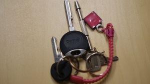 En nyckelknippa med en röd nyckelring som ligger på ett träfärgat bord.