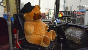 En nallebjörn som sitter vid ratten i en gammal buss.