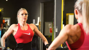 Linda Sonntag spääner musklerna framför spegeln