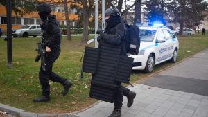 Svartklädda poliser med skyddsvästar springer.