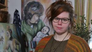 kvinna med målningar i bakgrunden