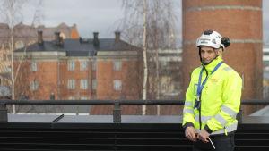 En man i varseljacka och skyddshjälm står på ett tak i Vasa.