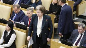 Valentina Teresjkova står bland bänkrader där människor sitter. Hon har brunt hår med en grå hårrand som går från pannan och bakåt över huvudet och bär en mörkt blågrönrutig kavaj.
