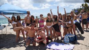 Ryhmä kevätlomalaisia poseeraa hiekkarannalla