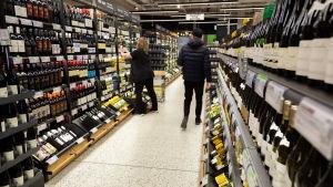 Alkon myymälän sisällä pulloja hyllyissä. Naismyyjä täyttää hyllyä ja asettaa juuri pulloja paikoilleen. Miesasiakas tummansinisessä toppatakissa ja musta pipo päässä kävelee ohi poispäin kamerasta.
