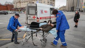 Ambulanspersonal tog hand om en äldre kvinna som kollapsade vid en busshållplats i centrum av Moskva i fredags. Det är oklart vad kvinnan led av.