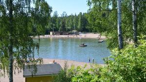 En större simgrop där två barn står vid stranden.