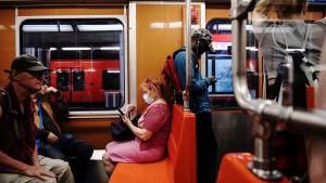 Personer åker metro i Helsinfors under en varm sommardag i slutet av juni 2020.
