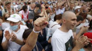 Människor applåderar och lyfter näven under ett stormöte