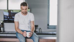 sorgsen men med kaffekopp sitter på en köksbänk