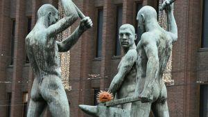 Skulpturen Tre smeder utanför Stockmann i Helsingfors. Under smedernas hammare har någon lagt en modell av ett coronavirus.