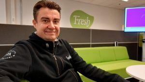En glad man sitter i en grön soffa i ett kontor