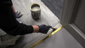 En hand med en pensel som målar ett golv.