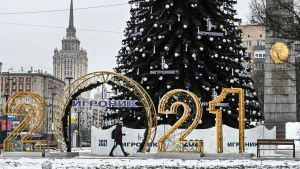 En ljusdekoration bildar talet 2021, i bakgrunden står en stor julgran.