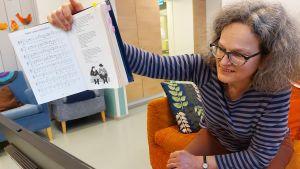 Sjukhusmusiker Anna Brummer leder en sångstund per distans på Tölö senioercenter under deras dagverksamhet. 2021.