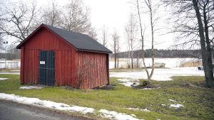 En röd, mindre byggnad som står på en gräsmatta i närheten av vattnet.
