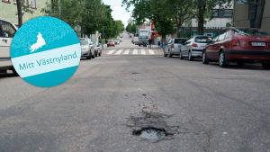 En gata med en grop i asfalten. Till vänster syns en logotyp där det står Mitt Västnyland.