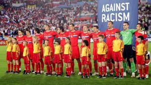 """Ryska landslaget poserar framför ett """"Against Racism""""-plakat."""