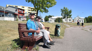 Två äldre personer sitter på en bänk i solen bredvid vattnet. Bakom dem syns hus i en stad.