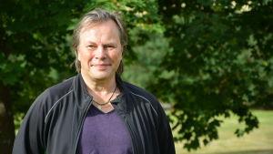 porträttbild av jan jacobson. han står ute i grönskan och bär en svart jacka över en lila t-skjorta.