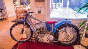 En speedwaymotorcykel i ett vardagsrum.