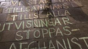Text skriven med gatukrita på trottoaren, där det står att utvisningar till Afghanistan ska stoppas.