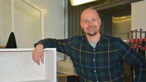 företagaren ben fredriksson lutar sig mot en av sina handgjorda möbler