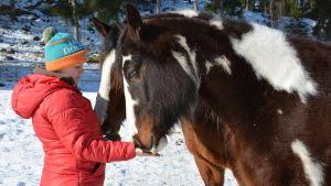 Kvinna i röd jacka står framför två hästar som har mulen i hennes hand.
