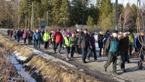 Många personer går längs en byväg en sen vårkväll med snö i dikena.