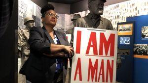 Museikurator Noelle Trent vid sidan av docka föfreställande renhållningsarbetare som kräver att bli behandlad som en mänska.
