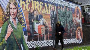En man går förbi en politisk väggmålning i näheten av Michael McGuinness hem i nordirländska Derry.