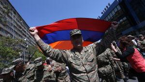 En soldat viftar med armeniska flaggan under en demonstration i Jerevan.