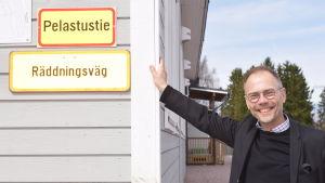 """Jukka Pietinen vid modulskolan i Sjundeå. På skolväggen n skylt där det står """"räddningsväg"""" på både finska och svenska."""