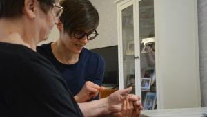 Ergoterapeut Anna Cederberg och Pirkko Paananen jobbar med att få tillbaka styrka och rörlighet i Pirkkos vänstra hand.