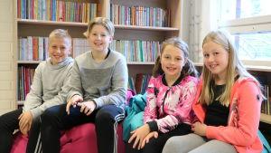 Fyra lågstadieelever, två pojkar till vänster och två flickor till höger sitter framför en bokhylla.