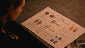 Merja Forsman tittar på ett stort papper på köksbordet, som berättar om deras koldioxidavtryck.